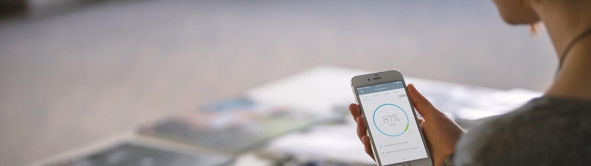 Frau benutzt sonnen App auf ihrem Handy um ihren Strom Verbrauch  zu ermitteln und somit Geld zu sparen
