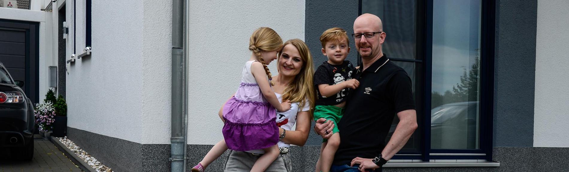 zufriedene Energiespeicher Kunden, vierköpfige Familie vor Ihrem Haus