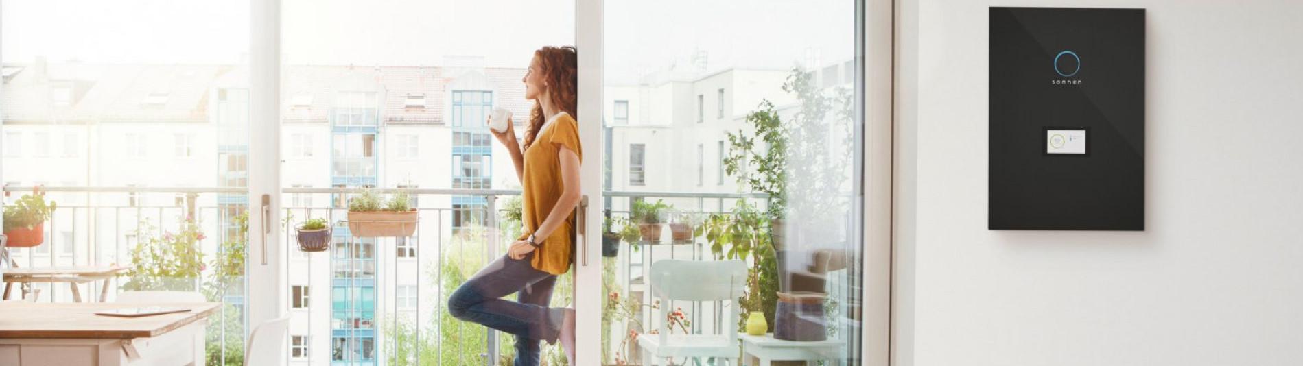Frau am Fenster macht sich unabhängig mit einem Energiespeicher sonnenBatterie und senkt somit ihre Kosten