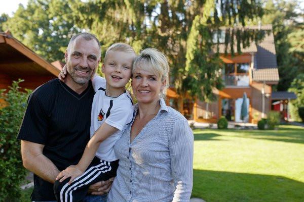 Familie im Sommer im Garten vor dem Haus mit PV-Anlage