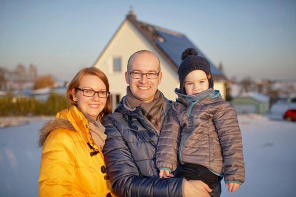 Familie vor dem Haus, mit Solaranlage und Heimspeicher