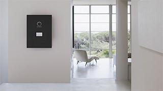 schwarze sonnenBatterie an der Wand hängend, im Hintergrund steht ein weißer Sessel vor einem großen Fenster