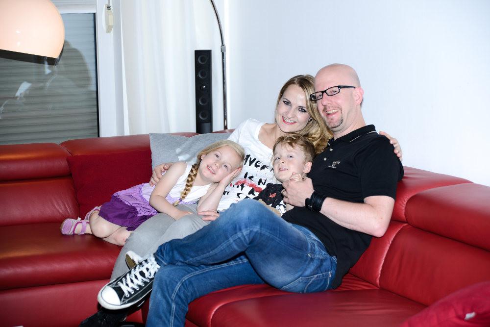 Mutter, Vater Tochter und Sohn auf dem roten Sofa in Ihrem Haus mit Solaranlage und Solarspeicher