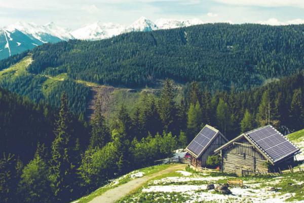 alm Landschaft mit einer Hütte die eine Photovoltaik Anlage auf dem Dacht hat