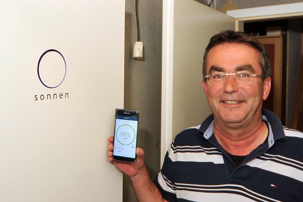 sonneBatterie Kunde vor seinem Stromspeicher mit Handy auf dem sie monitoring App geöffnet ist