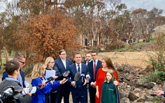Media and family in front of burnt property from 2020 Bushfires