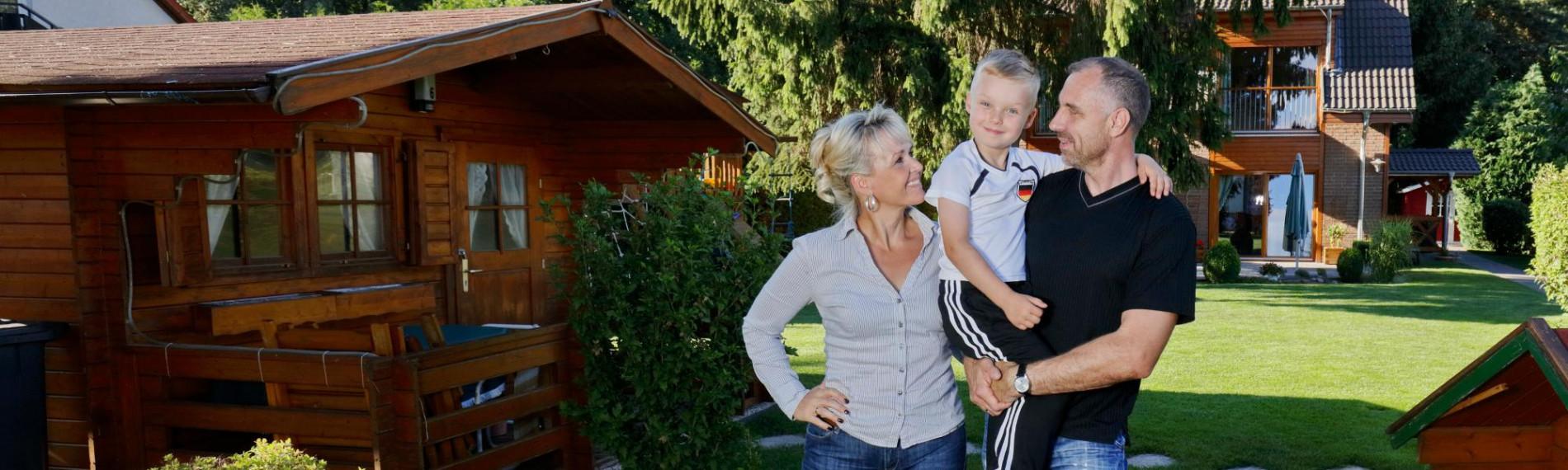 Mutter, Vater und Sohn im Garten vor dem Haus, zufriedenen sonnenBatterie Kunden