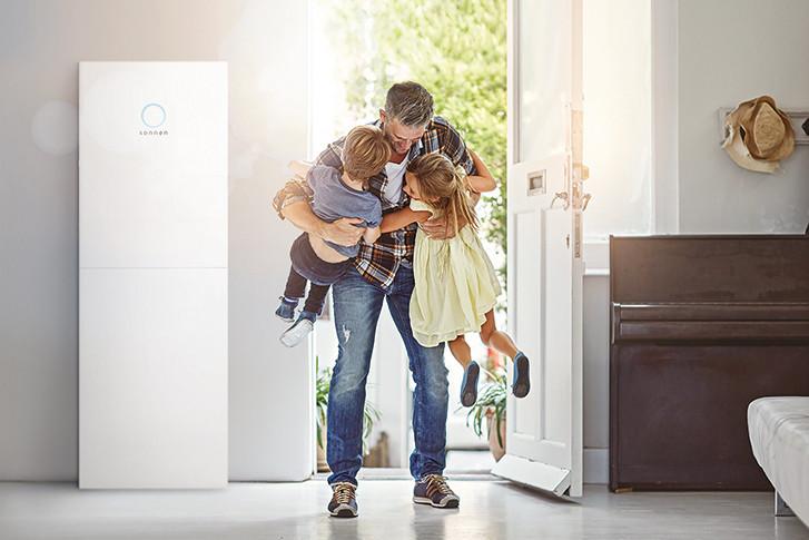Kinder empfangen Vater im Hauseingang mit sonnenBatterie