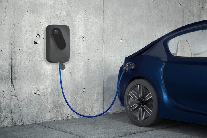 schwarzer sonnenCharger mit blauem Kabel an der Wand hängend, daneben ein blaues Auto, das aufgeladen wird