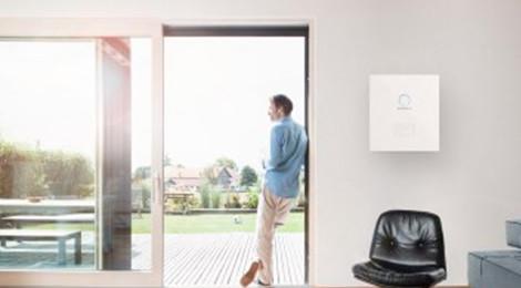 Mann am Fenster in seiner Wohnung macht sich unabhängig mit Solarstromspeicher sonnenBatterie