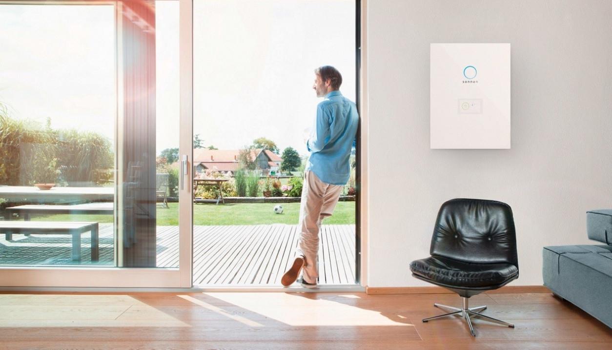 Mann steht in der Terassentür, neben ihm hängt eine sonnenBatterie an der Wand