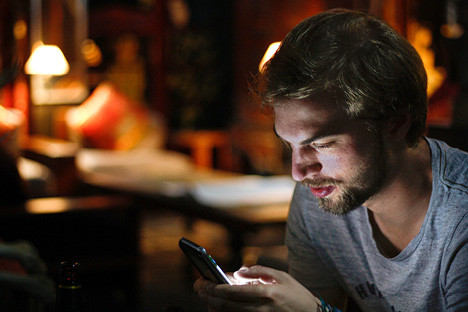 Man looking at his phone sitting in the dark