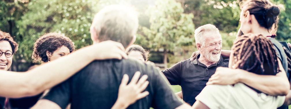 Un gruppo di persone in cerchio che si abbracciano