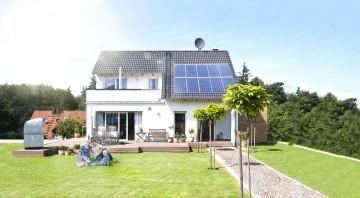 Familie sitzt im Garten auf der Wiese an einem sonnigen Tag und macht sich unabhängig und autark mit Heimspeicher sonnenBatterie und einer PV Solar Anlagae