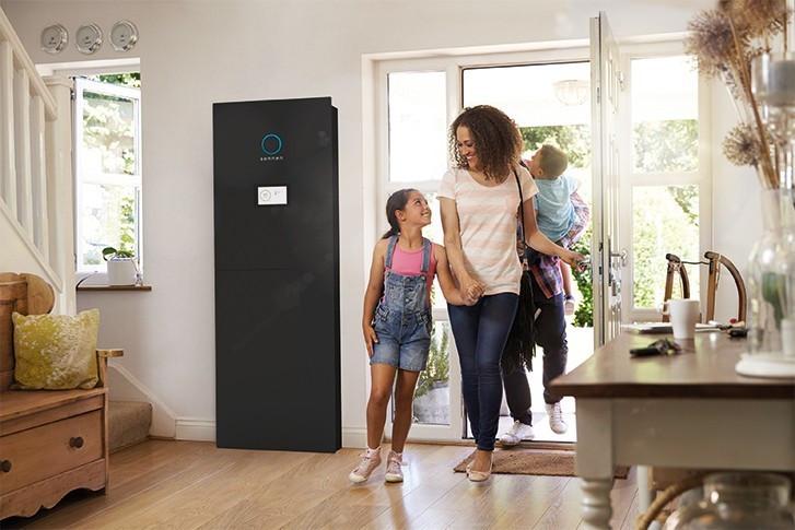 schwarze sonnenBatterie im Haus, Familie betritt das Haus, Mutter und Tochter schauen sich an und lachen