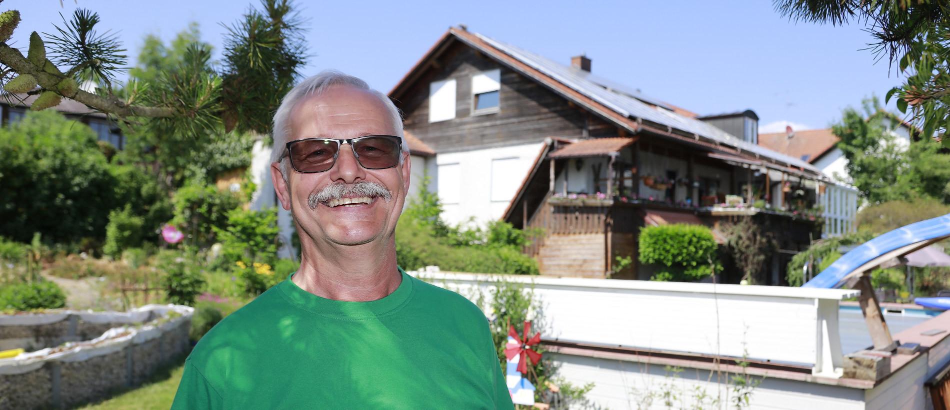 Herr Lacher vor seinem Haus mit PV Anlage & Stromspeicher