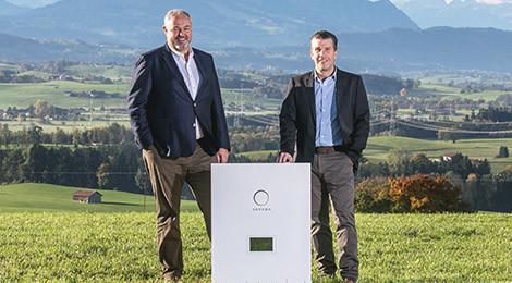 Torsten Stiefenhofer und Christoph Ostermann mit sonnenBatterie vor Landschaft